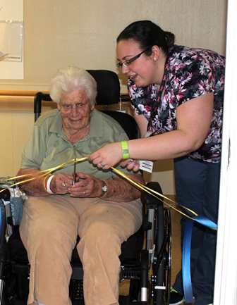 Patient and staff member cut the ribbon opening the ACE unit